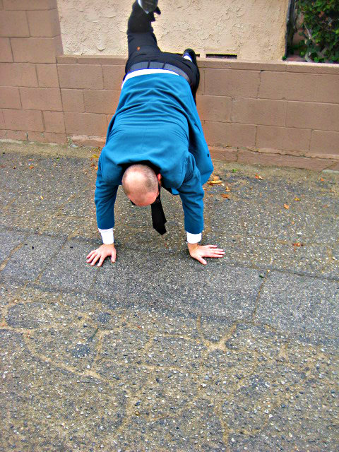 handstand against the wall revealing bald head